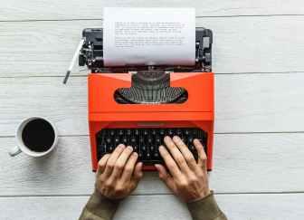 person holding black and orange typewriter