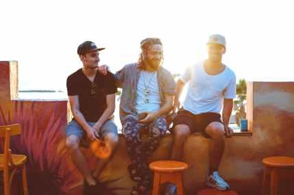 three men sitting on veranda