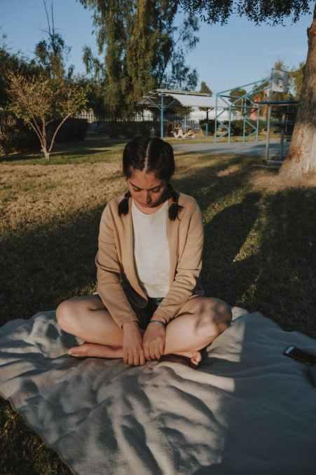 woman wearing in brown cardigan sitting on white mat
