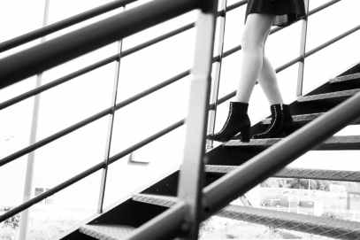 grayscale photography of woman walking on stairs